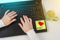 A note of text 14.02 written on a paper sticker. Background computer, laptop, woman`s hands on the keyboard. Stock Photos