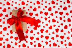 Valentine`s Day. Presented as a red ribbon on a white paper with red hearts. Valentine`s Day or a romantic event. Presented as a red ribbon on a white paper with Stock Photography