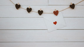 Valentine`s Day. Red and black hearts hangin on natural cord. Lowe letter. Wooden white background. Retro style. Valentines, hearts, hangin, on natural cord Royalty Free Stock Photography