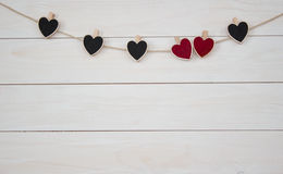 Valentine`s Day. Red and black hearts hangin on natural cord. Wooden white background. Royalty Free Stock Photo
