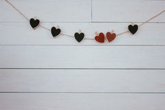 Valentine`s Day. Red and black hearts hangin on natural cord. Wooden white background. Retro style. Valentines hearts hangin on natural cord Wooden white Royalty Free Stock Image