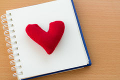 Valentine& x27;s Day with red heart. Open book and red heart on a wooden table Stock Photo