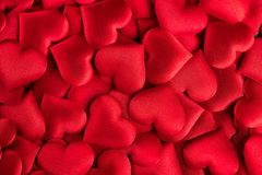 Valentine`s Day. Red heart shape backdrop. Abstract holiday Valentine background with red satin hearts. Love royalty free stock photo