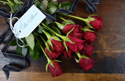 Valentine's Day red roses on dark recycled wood background with gift tag, Royalty Free Stock Photo