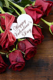 Valentine's Day red roses on dark recycled wood background - vertical Stock Photos