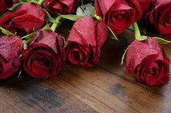 Valentine's Day red roses on dark recycled wood - closeup. Royalty Free Stock Photos