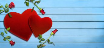 Valentine`s Day, red velvet hearts  and roses on blue wooden plank Stock Photo