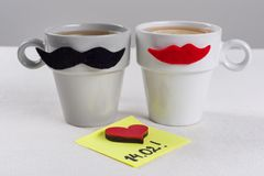 Valentine`s day romantic background. A couple of cups of black mustaches and red lips, note of text 14.02 written on a paper stic royalty free stock photo