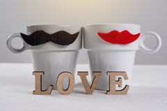 Valentine day romantic background. A couple of cups of black mustaches and red lips and a word of wooden letters - love. Valentine`s day romantic background. A Stock Photos