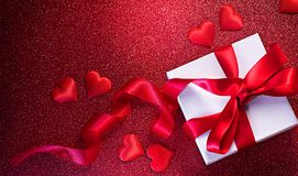 Valentine`s Day romantic background with gift box and red satin hearts. Gift box over holiday red glittering background with heart royalty free stock photography