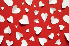 Valentine`s day romantic background. White paper hearts at red backdrop,. Top view stock photography