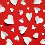 Valentine`s day romantic background. White paper hearts at red backdrop,. Top view royalty free stock images
