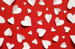 Valentine`s day romantic background. White paper hearts at red backdrop. Top view royalty free stock photo