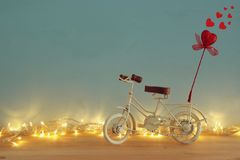 Valentine& x27;s day romantic background with white vintage bicycle toy and glitter red heart on it over wooden table. Royalty Free Stock Image