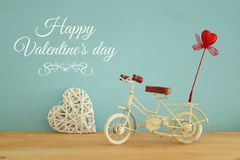 Valentine& x27;s day romantic background with white vintage bicycle toy and glitter red heart on it over wooden table. Valentine& x27;s day romantic background Royalty Free Stock Photos