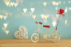 Valentine& x27;s day romantic background with white vintage bicycle toy and glitter red heart on it over wooden table. Stock Photos