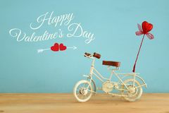 Valentine& x27;s day romantic background with white vintage bicycle toy and glitter red heart on it over wooden table. Stock Image