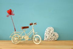 Valentine& x27;s day romantic background with white vintage bicycle toy and glitter red heart on it over wooden table. Royalty Free Stock Photography