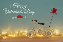 Valentine& x27;s day romantic background with white vintage bicycle toy and glitter red heart on it over wooden table. Royalty Free Stock Photo