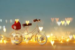 Valentine& x27;s day romantic background with white vintage bicycle toy and heart on it over wooden table. Valentine& x27;s day romantic background with white Stock Images