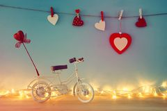 Valentine& x27;s day romantic background with white vintage bicycle toy and heart on it over wooden table. Valentine& x27;s day romantic background with white Royalty Free Stock Images