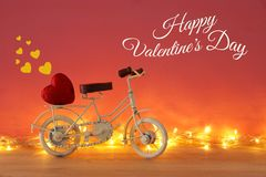 Valentine& x27;s day romantic background with white vintage bicycle toy and heart on it over wooden table. Valentine& x27;s day romantic background with white Royalty Free Stock Photography