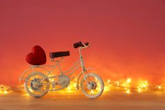 Valentine& x27;s day romantic background with white vintage bicycle toy and heart on it over wooden table. Valentine& x27;s day romantic background with white Royalty Free Stock Photos
