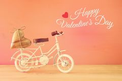 Valentine& x27;s day romantic background with white vintage bicycle toy and heart on it over wooden table. Valentine& x27;s day romantic background with white Royalty Free Stock Image