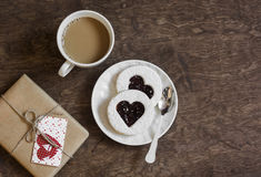 Valentine`s day romantic breakfast. Cookies-hearts with jam , coffee and a gift in craft paper on a wooden table, top view. Stock Image