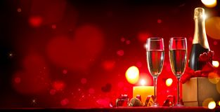 Valentine`s Day romantic dinner. Champagne, candles and gift box over red background Stock Images