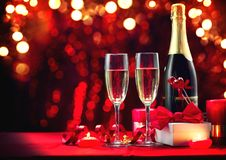 Valentine`s Day romantic dinner. Champagne, candles and gift box over holiday red background. Wedding celebrating. Birthday. Party royalty free stock image