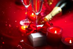 Valentine`s Day romantic dinner. Date. Champagne, candles and gift box over holiday background. Valentine`s Day romantic dinner. Date. Champagne, candles and stock images