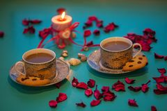 Valentine`s Day, romantic dinner - two vintage cups of coffee an. D cookies are standing on a green surface with pink rose petals next to  burning candle with a Royalty Free Stock Photos