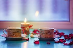 Valentine`s Day, romantic dinner - two vintage cups of coffee. Are standing on a green surface with pink rose petals next to  burning candle with a heart symbol Stock Photos