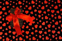 Valentine`s Day. Presented as a red ribbon on a black paper with red hearts. Valentine`s Day or a romantic event. Presented as a red ribbon on a black paper with Royalty Free Stock Images