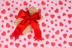 Valentine`s Day. Presented as a red ribbon on a pink paper with red hearts. Valentine`s Day or a romantic event. Presented as a red ribbon on a pink paper with Royalty Free Stock Image