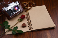 Valentine's Day - Rose, chocolates and camera on notebook Royalty Free Stock Photography