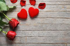 Valentine`s Day, roses and hearts on old wooden table Royalty Free Stock Images