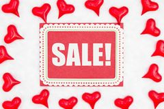 Valentine`s Day sale message on greeting card with red hearts on white fabric. Valentine`s Day sale message on greeting card with red hearts on textured white royalty free stock photo