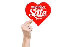 Valentine's Day and sale topic: Hand holding a card in the form of a red heart with the word Sale isolated on white background. In studio Stock Photography