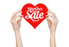 Valentine's Day and sale topic: Hand holding a card in the form of a red heart with the word Sale isolated on white background. In studio Stock Photo