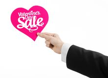 Valentine's Day and sale topic: Hand of a man in a black suit holding a card in the form of a pink heart with the word Sale Stock Photography