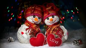 Valentine`s Day. Lovers of snowmen are in the snow and keep the hearts of the fabric. Valentine`s Day. Snowmen love couple set against each other. Snowmen in stock footage