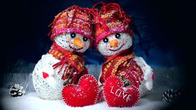 Valentine`s Day. Snowmen in love stand on the snow and keep their hearts out of felt on a dark background. Valentine`s Day. Snowmen love couple set against each stock footage