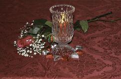 Valentine`s day table with rose, candle and candy. Red rose, crystal hurricane candle and heart shaped chocolates on red tablecloth Stock Photos