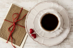 Valentines day tea set with cup of coffee and gree. Valentine or birthday celebration tea set with cup of coffee, couple red hearts and greeting card Royalty Free Stock Image