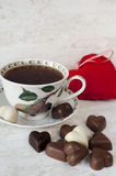 Valentine's day tea time still life with heart shaped chocolates. Valentine's day still life. Cup of tea with heart shaped chocolates on gray wooden background Stock Photos