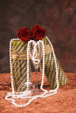 Valentine's day theme. Of two candles, two red rosebuds, two champagne glasses, and a string of pearls draped over them Stock Image
