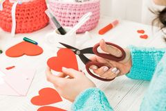 Valentine's day theme. Female hands cut the heart out of the pap. Er. Packed gifts, tools on a battered wooden table. Workplace for the preparation of handmade royalty free stock photos