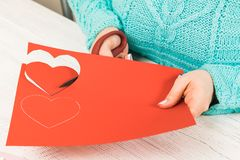 Valentine's day theme. Female hands cut the heart out of the pap. Er. Packed gifts, tools on a battered wooden table. Workplace for the preparation of handmade stock photo